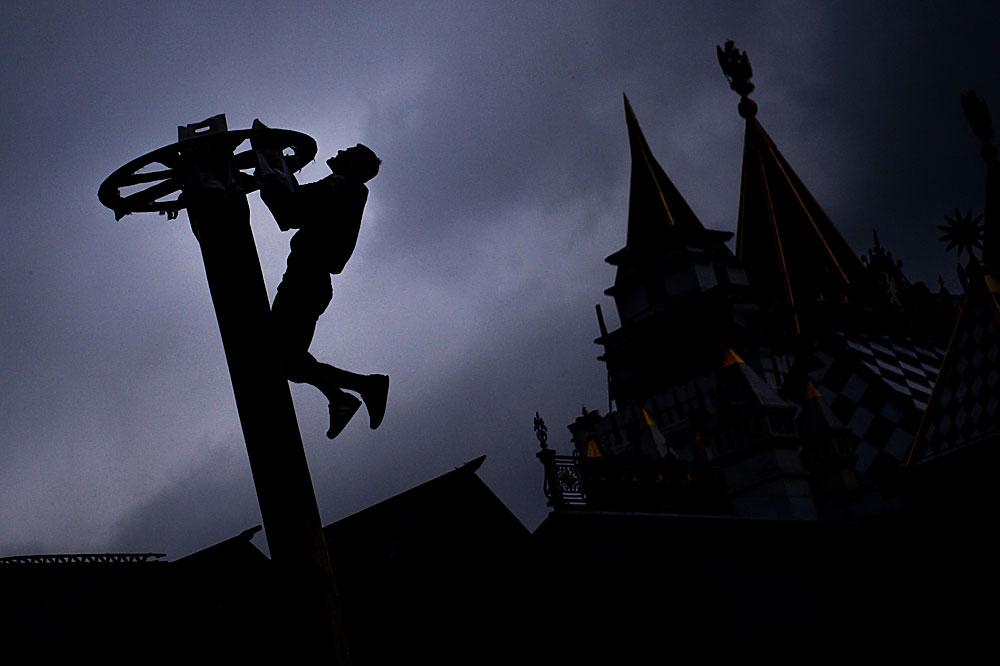 Мъж се катери по стълб в последния ден на празничните мероприятия, посветени на Масленица, в Измайловския кремъл в Москва.