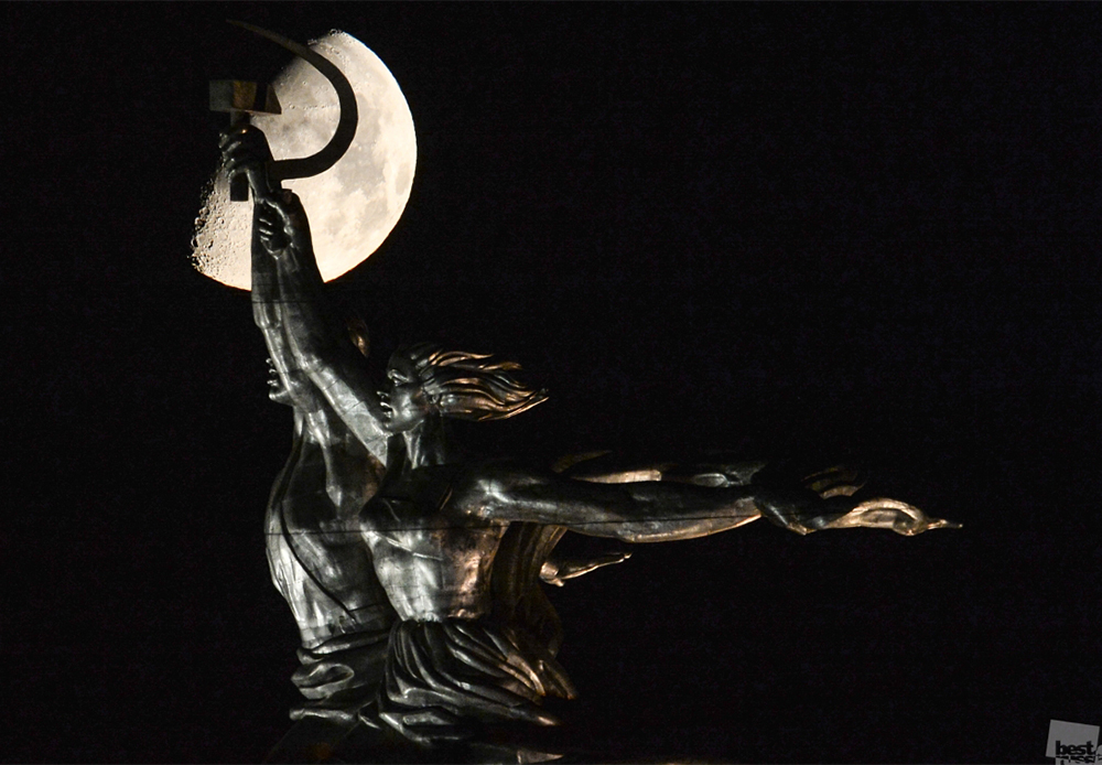 "The moon rises above the ""Worker and Kolkhoz Woman"" monument in VDNH exhibition center, Moscow."