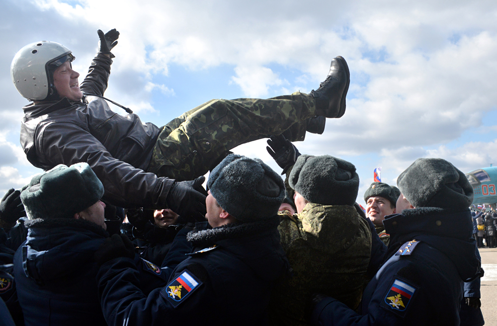 VORONEZH REGION, RUSSIA. MARCH 15, 2016. Russian military officers lift up a pilot of a Russian Air Force Sukhoi Su-34 fighter bomber, one of the first group of Russian military aircraft to return from Syria following an operation against the ISIL and other terrorist groups, during the arrival ceremony at a military installation in Voronezh Region. The Russian president has announced the withdrawal of the main part of Russia's military contingent from Syria, starting on March 15, 2016.