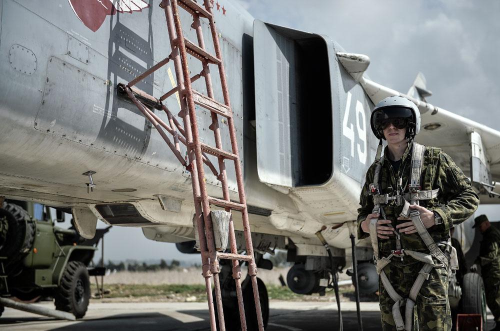 Seorang pilot Angkatan Udara Rusia di samping pesawat multiperan Su-24 di Pangkalan Udara Hmeimim, di Provinsi Latakia, Suriah.
