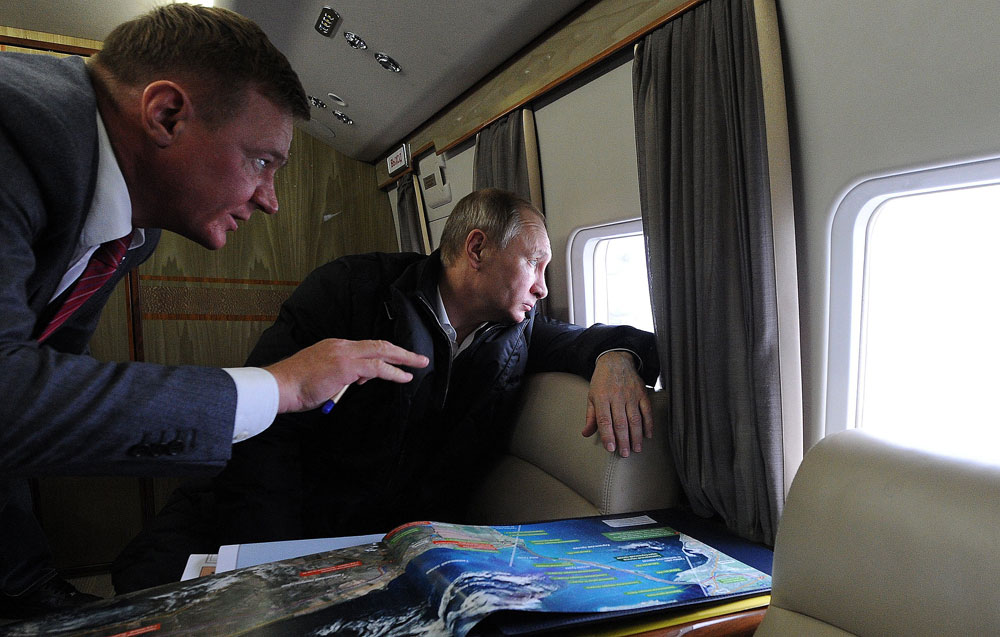 Russian President Vladimir Putin (R) and Rosavtodor Federal Highway Agency head Roman Starovoit (L) inspect the the bridge connecting Taman and Kerch while in flight over the Kerch Strait in Russia