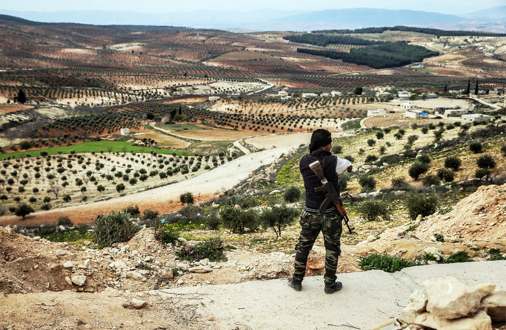 An armed Kurdish fighter surveys the area from an elevation near the town of Azaz on the Syrian-Turkish border.