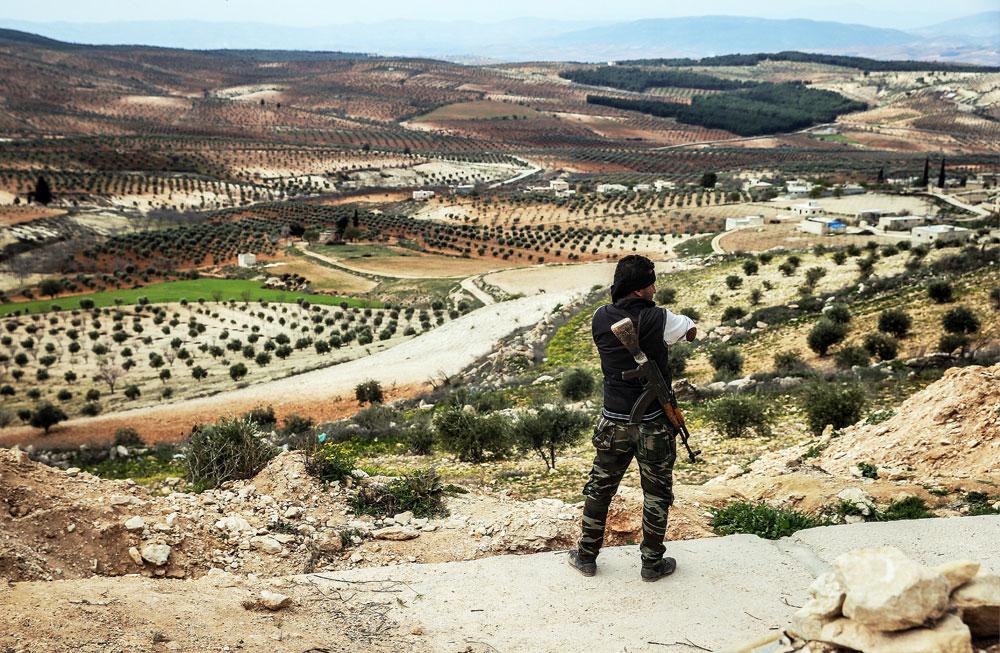 Oboroženi kurdski borec s hribčka v bližini mesta Azaz na sirsko-turški meji opazuje dogajanje. Fotograf: Valerij Šarifulin/TASS