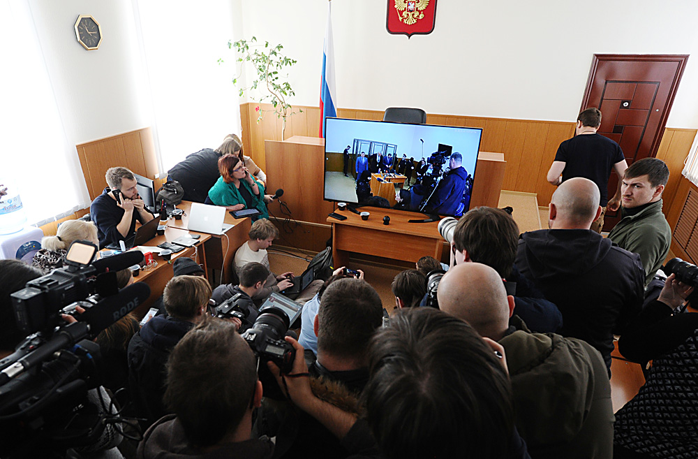 Journalists watch closed-circuit television transmitting the image from a courtroom at the Donetsk City Court. The court is to begin the announcement of the verdict in the case of Ukrainian citizen Nadezhda Savchenko on March 21.