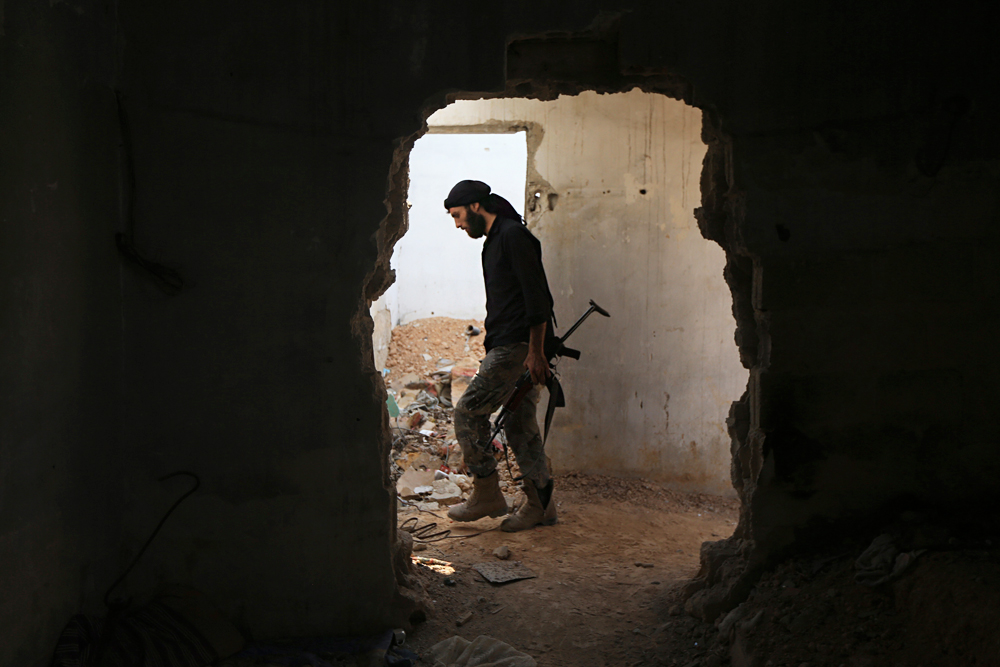 A fighter from the Free Syrian Army's Al Rahman legion carries his weapon as he moves inside a damaged building on the frontline against the forces of Syria's President Bashar al-Assad in Jobar, a suburb of Damascus.