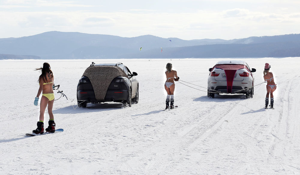 Bikini-clad women ski and snowboard as they are led by cars during a performance on the frozen Yenisei River outside Krasnoyarsk, Siberia, Russia