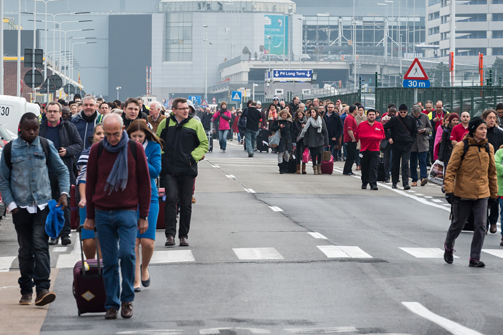 People walk away from Brussels airport after explosions rocked the facility in Brussels, Belgium, March 22, 2016.