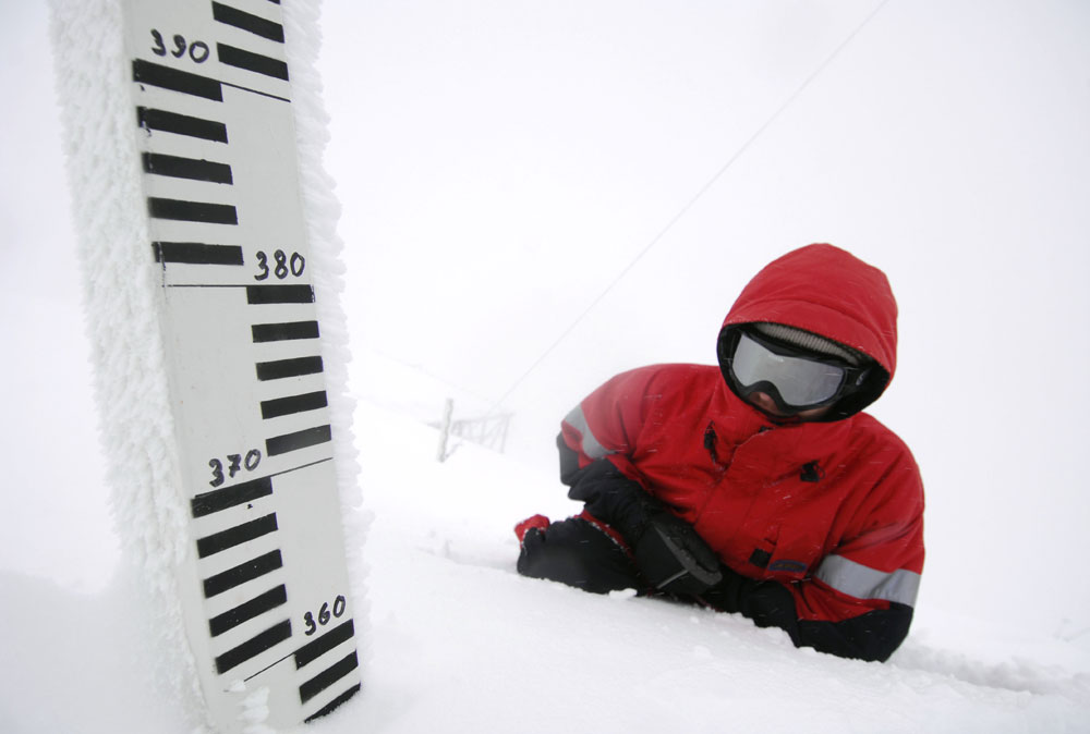 An employee measures the snow cover depth at the Aibga weather station in the Caucasus Mountains outside Sochi.