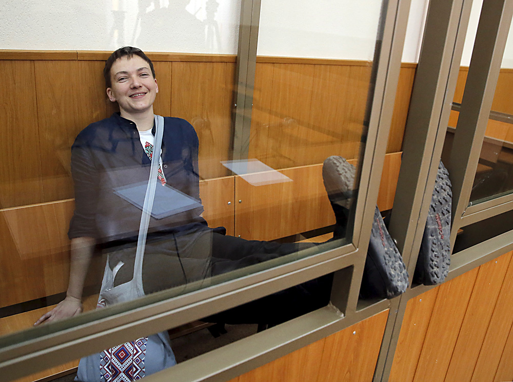 Former Ukrainian army pilot Nadezhda Savchenko smiles from a glass-walled cage during a verdict hearing at a court in the southern border town of Donetsk in the Rostov region, Russia, March 22, 2016.