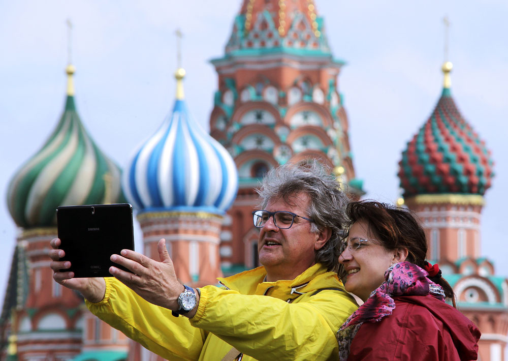 International tourists using a tablet to take a picture by the St. Basil's Cathedral in Red Square.