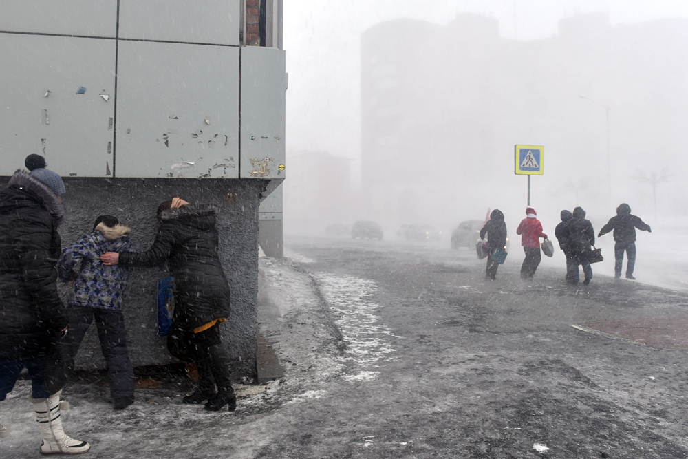 Passanten kämpfen gegen orkanartige Böen in den Straßen von Norilsk an. Der Wind war gestern so stark, dass er eine am Flughafen parkende Boeing-737 seitwärts um 180 Grad drehte.
