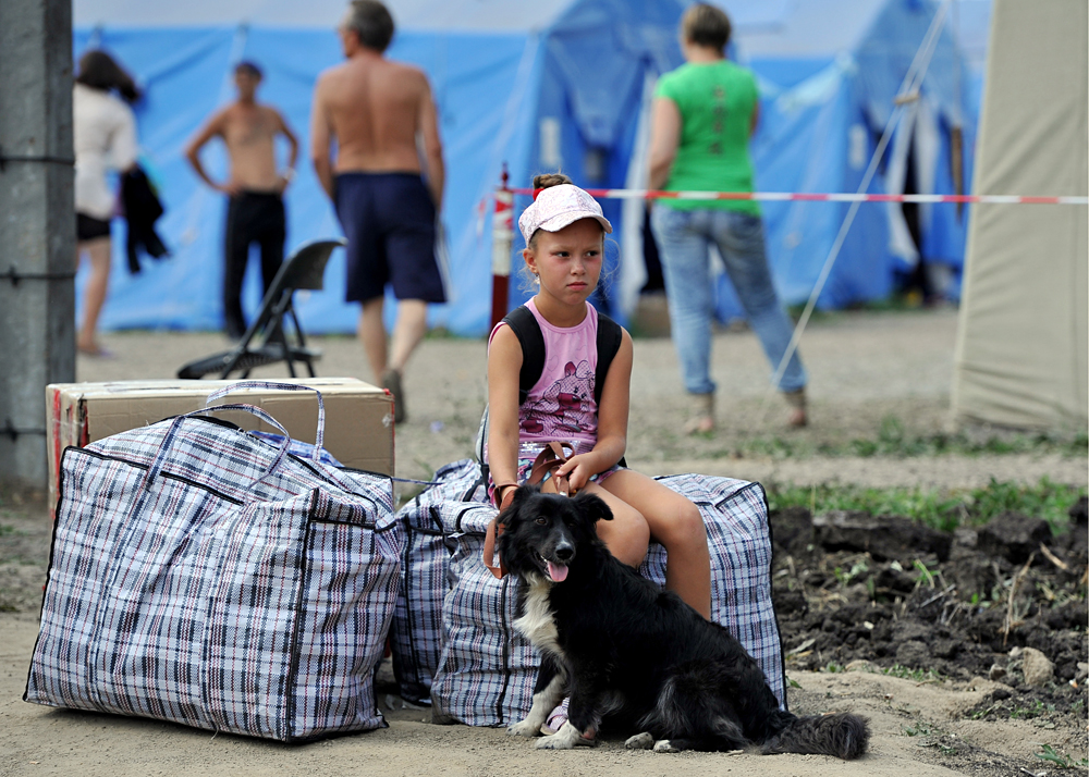 A girl with a dog sits by her belongings in a camp for Ukrainian refugees near Gukovo crossing on the Russian-Ukrainian border, 2014