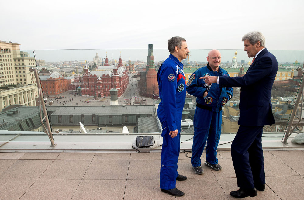 Red Square is visible in the background as Secretary of State John Kerry meets with American astronaut Scott Kelly, second from right, and Russian cosmonaut Mikhail Korniyenko on the roof of the Ritz-Carlton Hotel in Moscow, Russia