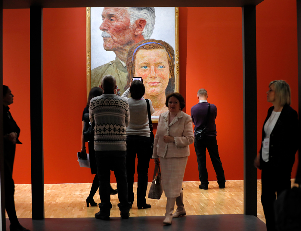 Visitors and journalists study a painting at the first major monographic exhibition of Geliy Korzhev in the Tretyakov gallery in Moscow, Russia. Geliy Korzhev was a painter in Soviet approved style of Socialist Realism, he continued to be active after the dissolution of the Soviet Union and remained a supporter of Communism