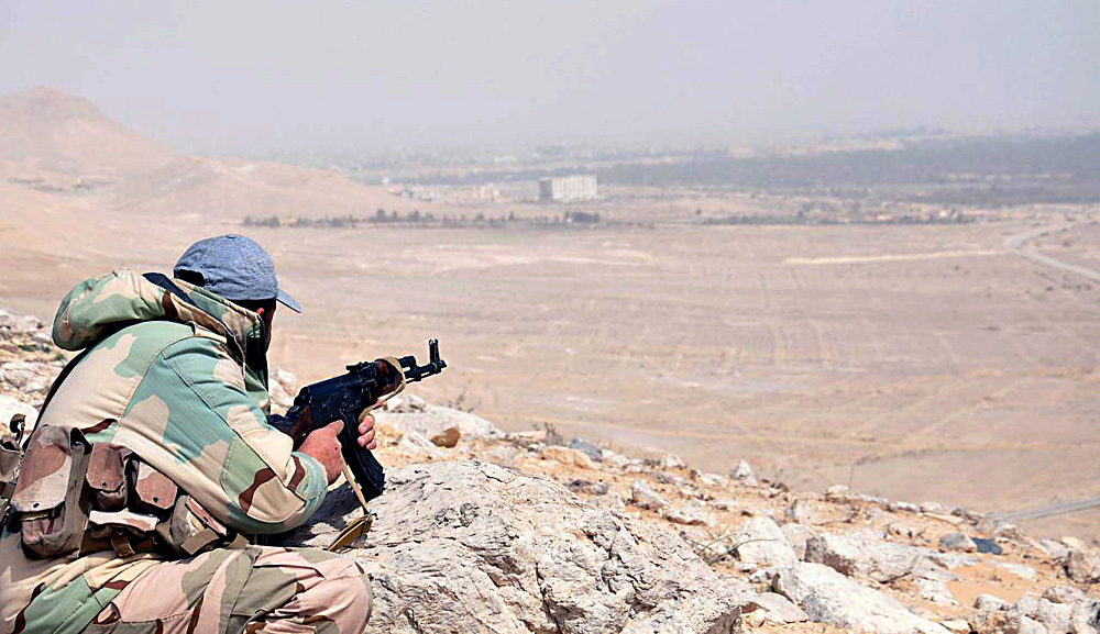 A member of the Syrian army taking position during an advance further in the vicinity of the ancient city of Palmyra, in central Homs province, March 24, 2016.