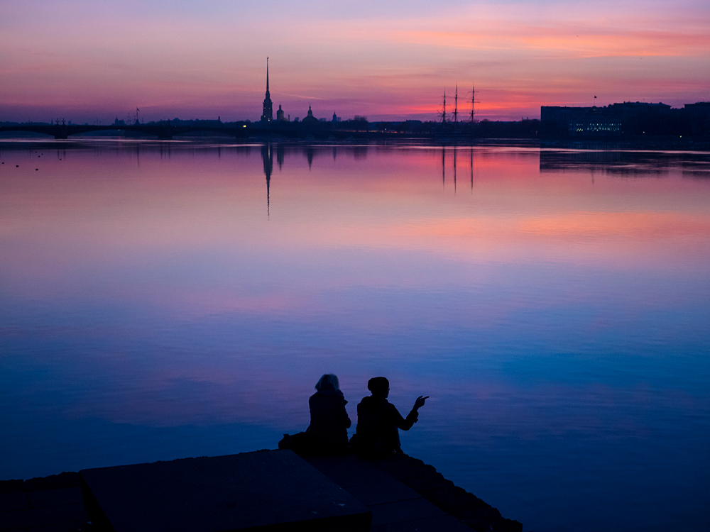 Ein Pärchen genießt den Sonnenuntergang über der Peter-und-Paul-Festung in Sankt Petersburg.