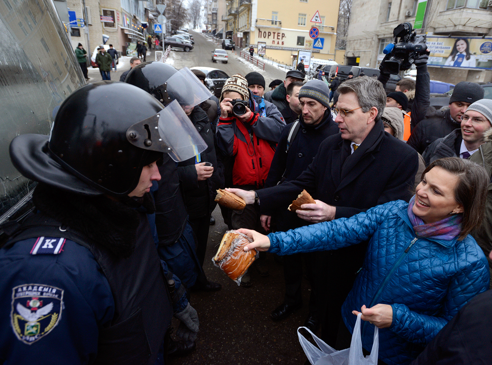 Victoria Nuland and Geoffrey Pyatt distribute bread to riot police near Independence square in Kiev December 11, 2013. Source: Reuters