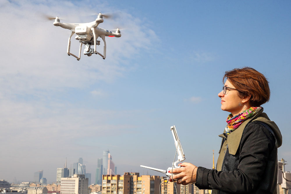 A girl flies a drone from a rooftop in Moscow. Russia introduces obligatory registration of unmanned aircraft weighing over 250 grams starting April 1, 2016