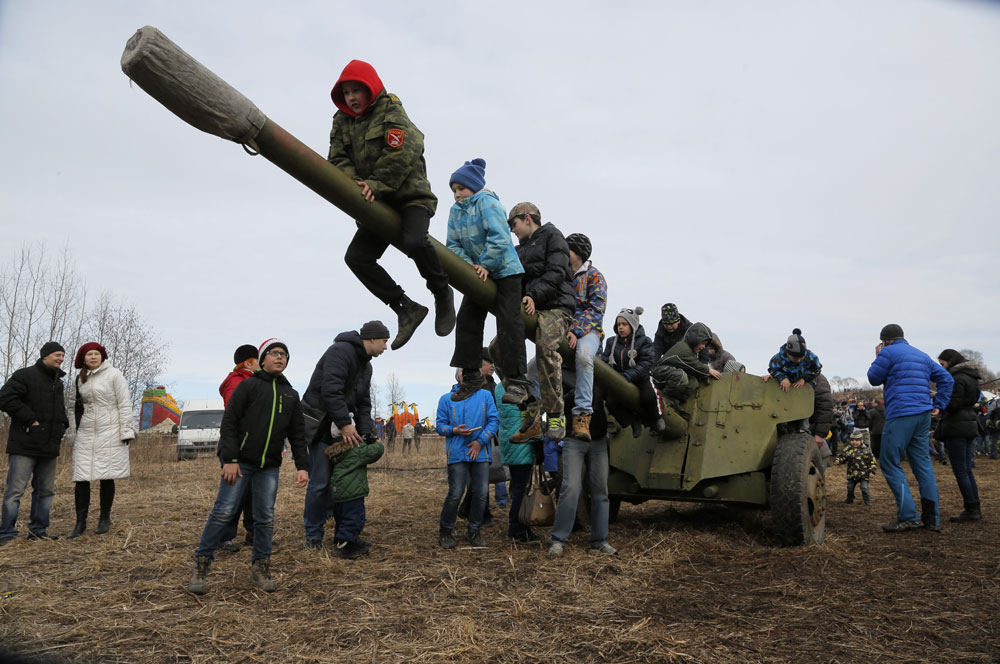 Children play at a cannon during a military show outside St.Petersburg, Russia, Sunday, April 3, 2016.