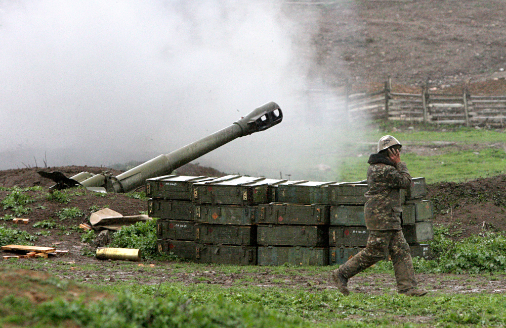A howitzer fires at an artillery position of the self-defense army of Nagorno-Karabakh near Martakert, Azerbaijan, Sunday, April 3, 2016.