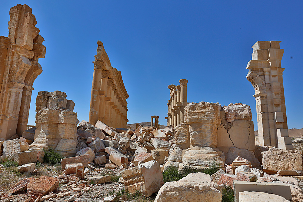 In this picture taken on April 1, 2016, damage is seen in the ancient city of Palmyra in the central city of Homs, Syria. Explosions rocked the ancient town of Palmyra on Friday and on the horizon, black smoke wafted behind its majestic Roman ruins, as Syrian army experts carefully detonated hundreds of mines they say were planted by Islamic State militants before they fled the town.