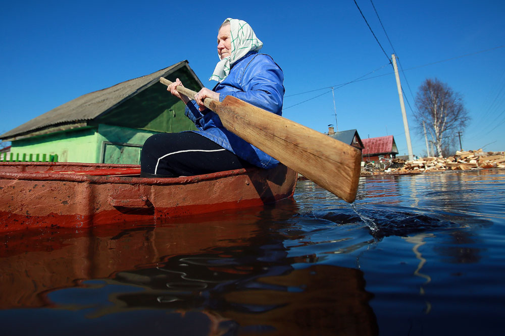 A resident of the village of Kholui paddling to reach her house. Due to the rising waters of the Teza River, several houses in the village were flooded.