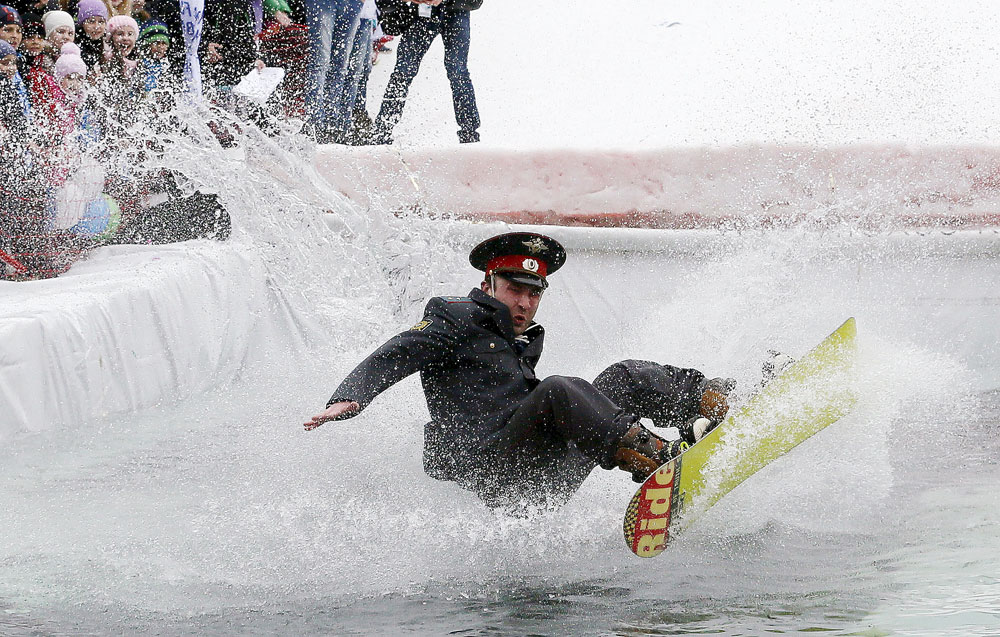 A snowboarder, wearing a costume of a Russian Interior Ministry officer, falls down in an attempt to cross a pool of water at the foot of a ski slope at the Bobrovy Log ski resort on the suburbs of the Siberian city of Krasnoyarsk, Russia