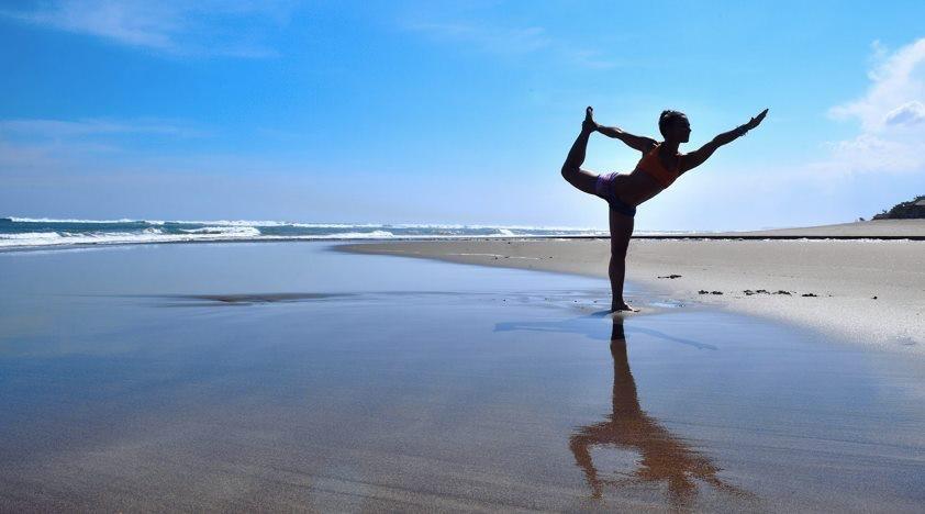 Seorang warga Rusia melakukan yoga di pantai Bali.
