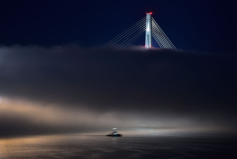 Night mist over Vladivostok, Russia. Mist covers Russky Bridge across the Eastern Bosphorus Strait