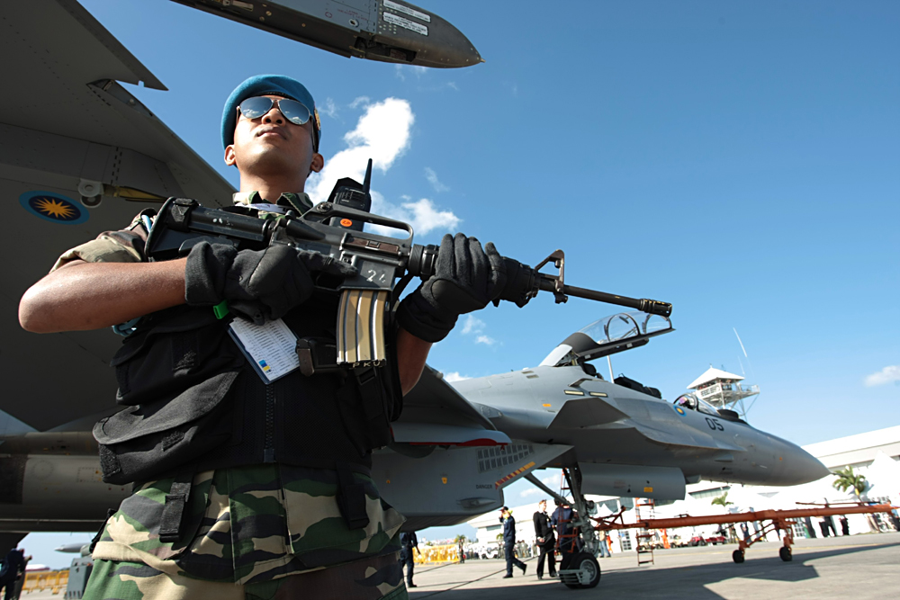 Malaysian soldier armed with rifle stands on guard near Royal Malaysian Air Force Sukhoi Su-30MKM jet fighters at the 2007 Langkawi International Maritime & Aerospace Exhibition (LIMA 2007) in Malaysia.