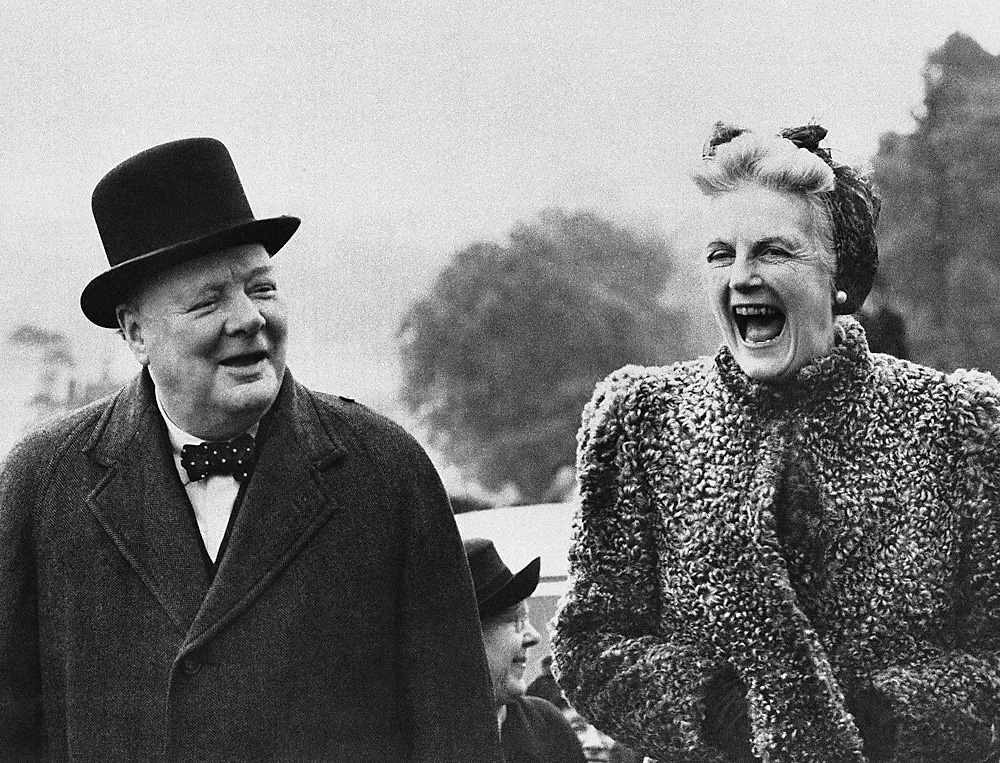 Mrs. Clementine Churchill laughs heartily as British Prime Minister Winston Churchill talks at Chigwell, England, during his election campaign, May 27, 1945.