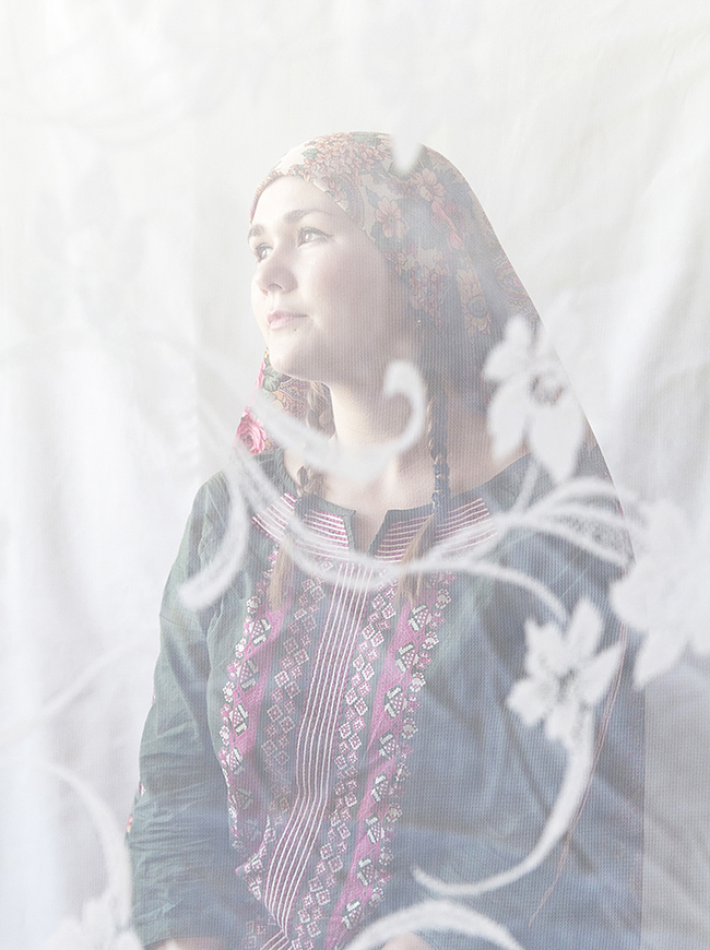 "Photographed through lace curtains, like through a bridal veil, women are visible through the screen of another cultural tradition. In the photos, these women are depicted as a ""Tatar Madonna."" / Oxana, 23, art school teacher. ""My grandmother was Tatar. I always regard myself as Russian, but I often was called 'Eastern'. My natural hair color is light brown, but I often dyed it black. Probably subconsciously I was highlighting my 'Eastern' roots""."