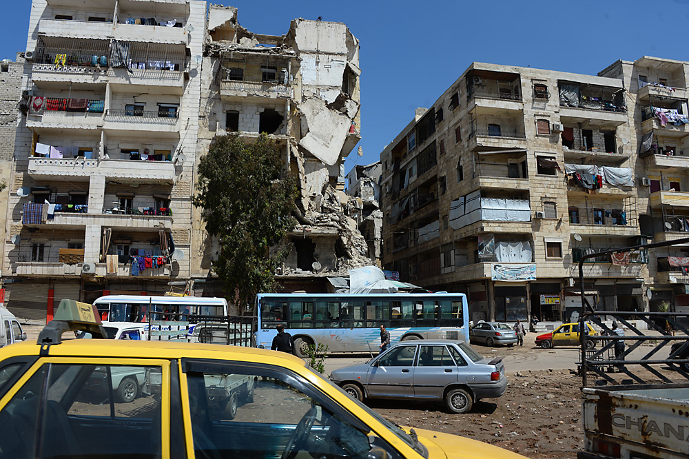 Sírios permanecem em edifícios destruídos do bairro de Salah ad-Din, em Aleppo, um dos mais afetados pela guerra