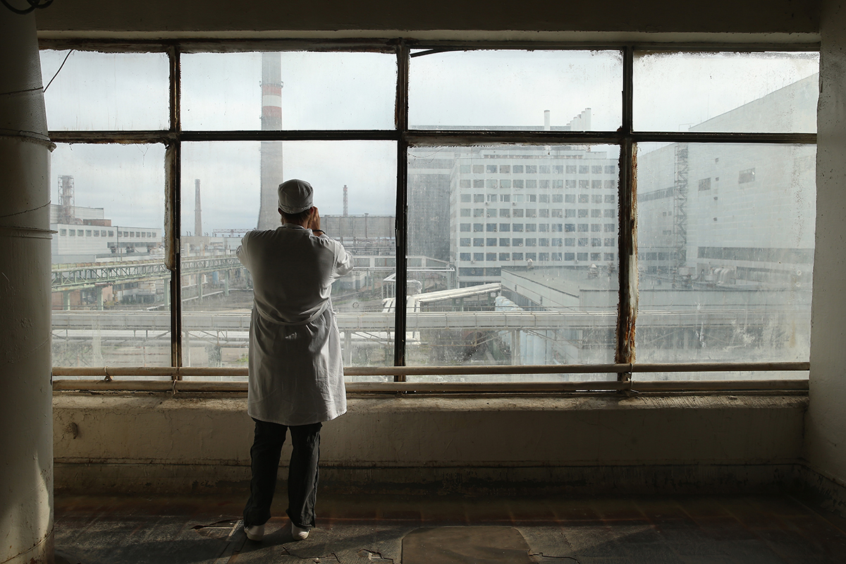 A tourist takes pictures of the first and second reactors of the Chernobyl nuclear station on September 29, 2015. The exclusion zone around the plant has seen around 40 thousands of tourists in the last 10 years. However, the radiation background still exceeds normal values by up to 30 times.