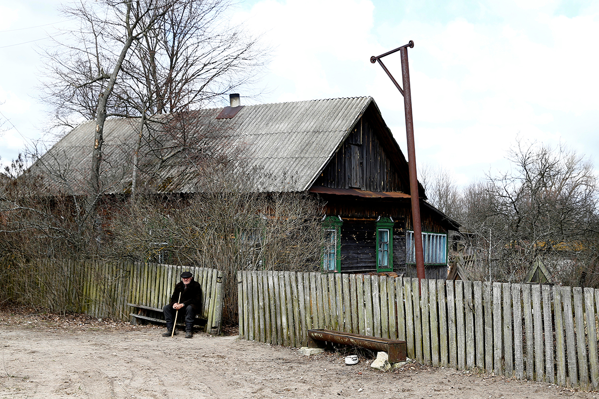 Ivan Shamyanok sits in front of his house in the village of Tulgovichi, near the exclusion zone.