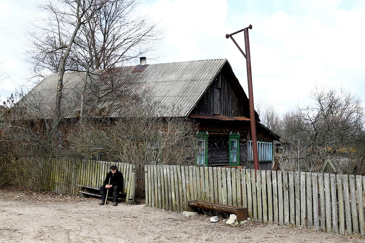 Ivan Šamjanok sjedi ispred svoje kuće u selu Tulgoviči, nedaleko od zatvorene zone.