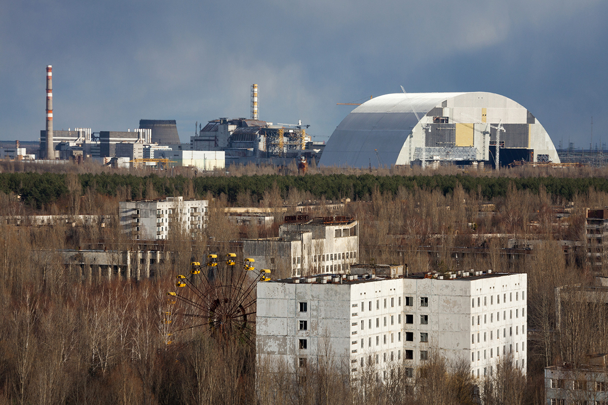 A view of the abandoned town of Pripyat, Ukraine (3 km from the nuclear station), March 19, 2016. The nuclear plant is seen in the background as well as the confinement meant to capture radioactive release.