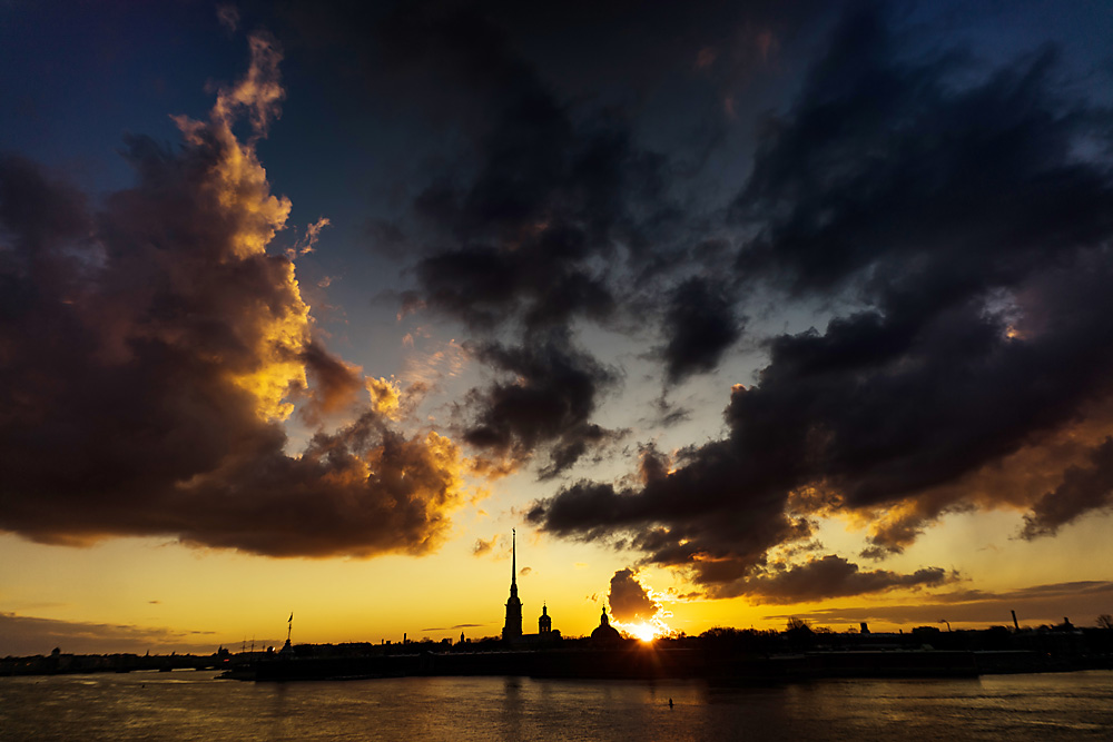 Sunset over an embankment of the Neva River. Background: Peter and Paul Cathedral and the Peter and Paul Fortress.