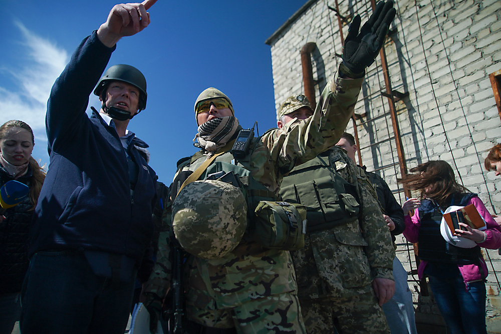 Alexander Hug, chief monitoring mission of OSCE in Ukraine (left) and Ukrainian military servicemen, members of Joint Center for Control and Coordination mission point at a side of the newly installed OSCE surveillance camera to register violations of ceasefire in Avdiivka, eastern Ukraine, April 16, 2016.