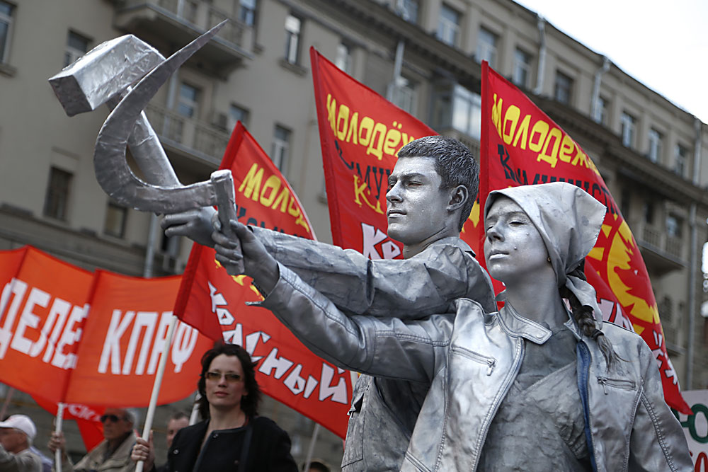 Russian Communist party members and supporters, with two of them performing as a living workers' statue holding the iconic communist symbols of hammer and sickle, join the traditional May Day demonstration, Moscow, Russia, 01 May 2016. Labor Day, or May Day, is observed all over the world on the first day of May to celebrate the economic and social achievements of workers and fight for laborers rights