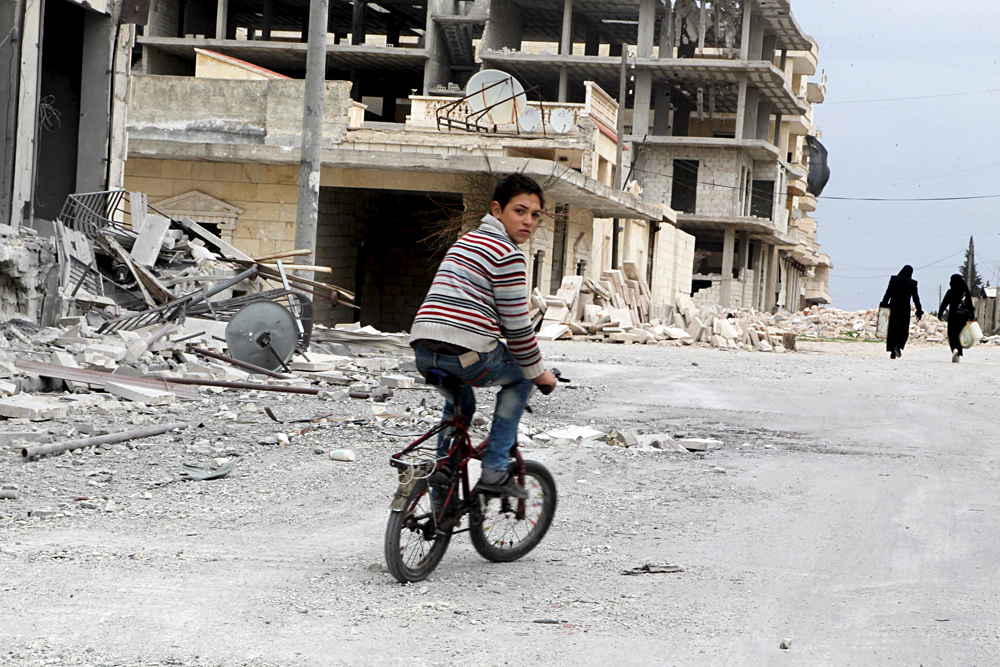 A boy rides a bicycle near damage in Kafr Hamra village, northern Aleppo countryside, February 27, 2016.