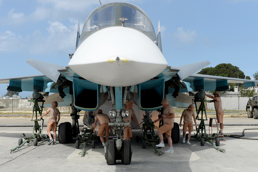 Russian servicemen prepare an Su-34 fighter jet for a mission from the Russian Hmeimim military base in Latakia province, in the northwest of Syria on May 4, 2016.