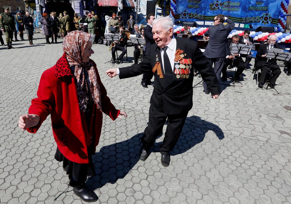 """Ветеранот од 2 Светска војна Анатолиј Замјатин, 91, учествува во манифестацијата Танц под отворено небо во предвечерието на Денот на Победата во паркот """"Гагарин"""". 5 мај 2016, Краснојарск, Сибир, Русија."""