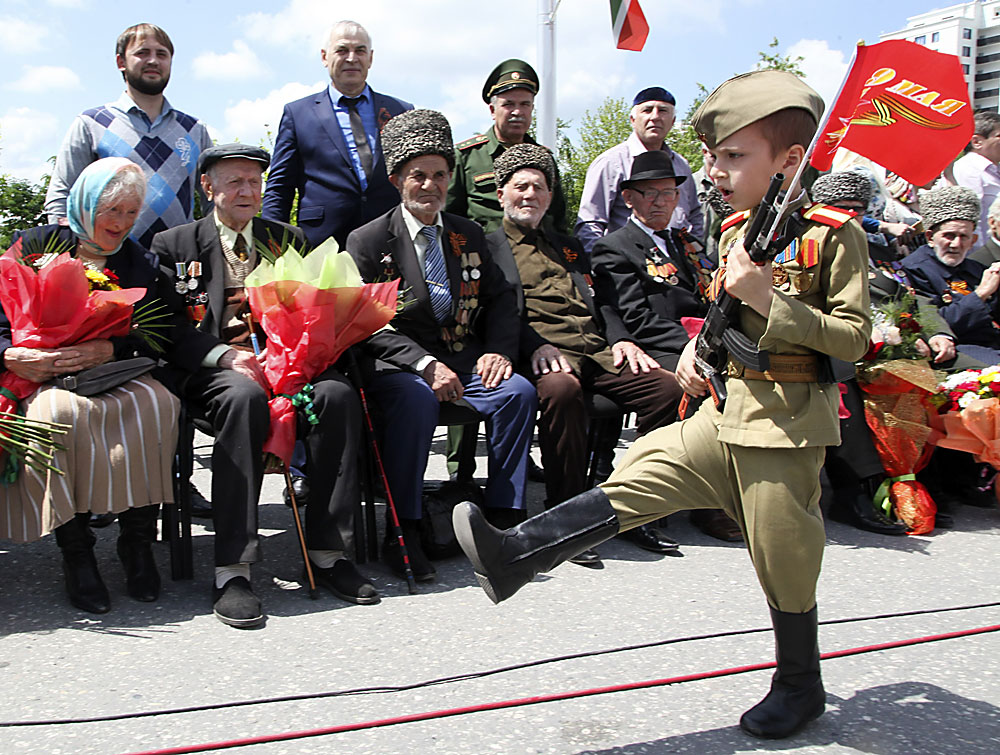 A Chechen boy dressed in a WWII era Soviet uniform, marches with a red flag, with a sign reading May 9, during Victory Day celebrations in Chechnya's provincial capital Grozny, Russia, Monday, May 9, 2016. Russia celebrates the 71st anniversary of the victory over the Nazi Germany in the World War II on Monday.