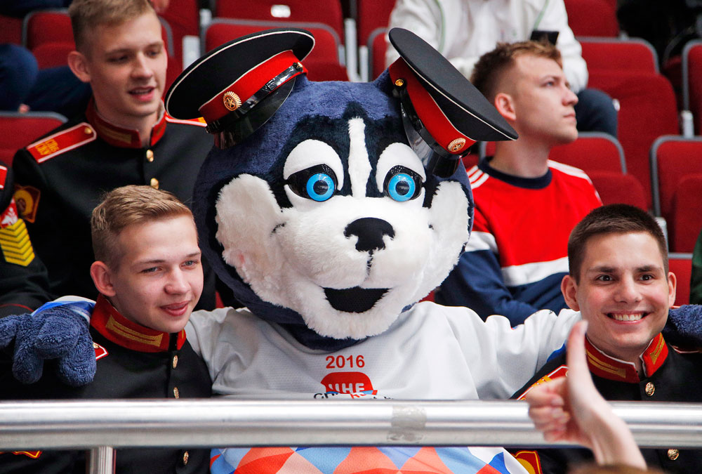 A mascot of Championships Laika sits among cadets during the Hockey World Championships Group B match between France and Belarus in St.Petersburg, Russia