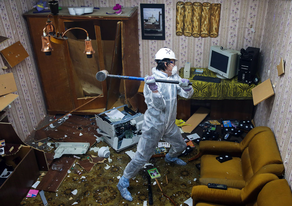 A man in a hard hat smashes household objects in a rage room. The Debauch stress relief service gives its customers an opportunity to smash the rage room up with sledgehammers and bats to relieve stress and tension.