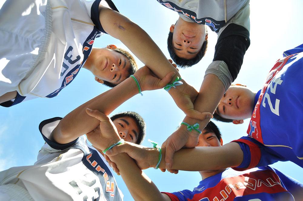 Nachwuchsspieler aus FC Tokyo tauschen ihre Armbu00e4nder miteinander.