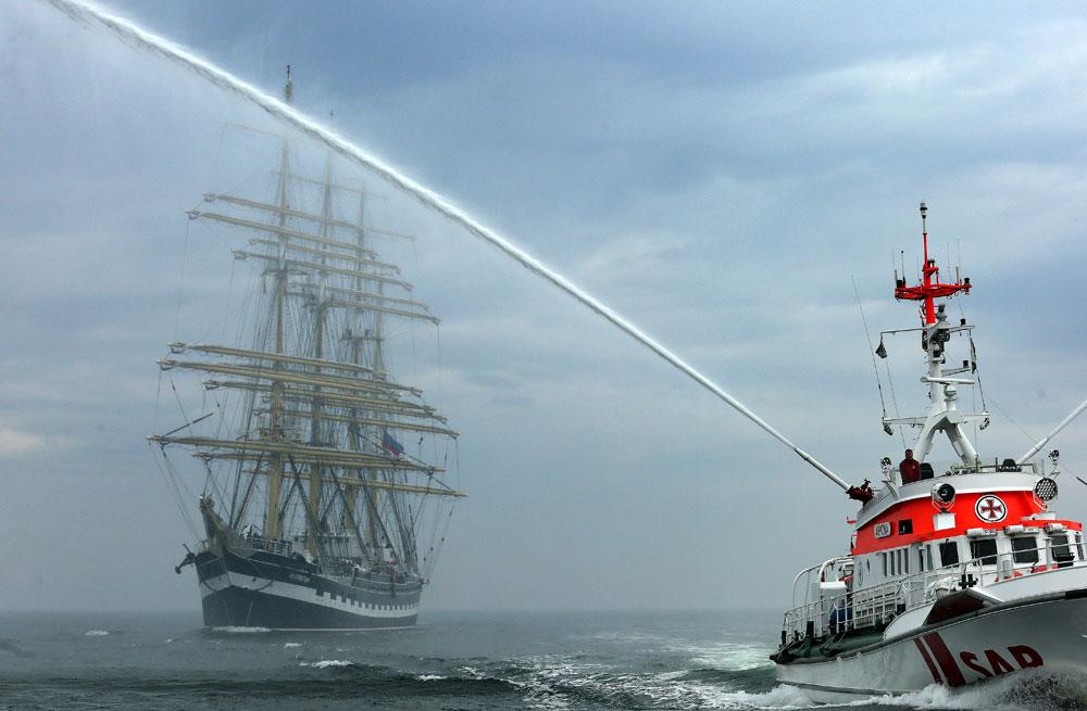 "Приветстван c водни струи, руският ветроходен кораб ""Крузенщерн"" пристига в Росток, Германия."