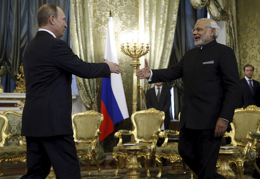 Russia's President Vladimir Putin (L) shakes hands with India's Prime Minister Narendra Modi during a meeting at the Kremlin in Moscow, Russia