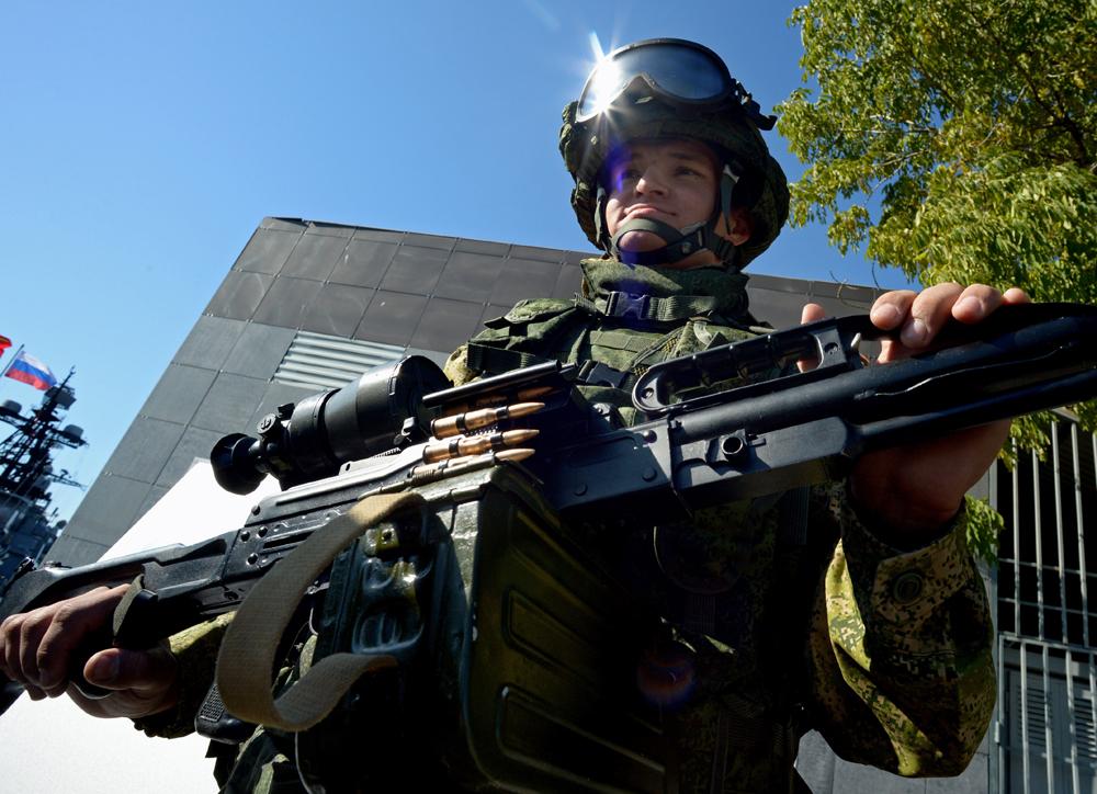 Seorang tentara dari Angkatan Laut Rusia memamerkan senapan mesin Pecheneg pada pameran senjata dan peralatan khusus di Hari Inovasi Distrik Militer Timur Day di Vladivostok.